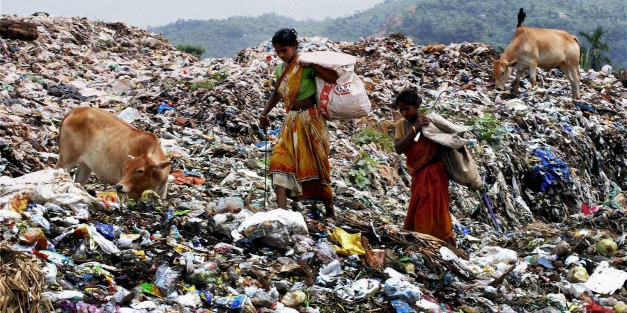 Waste collectors walking through the dump yard without any safety precautions